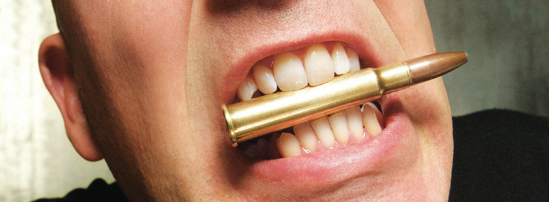 English Idioms you should know: a man bites a bullet between his teeth.