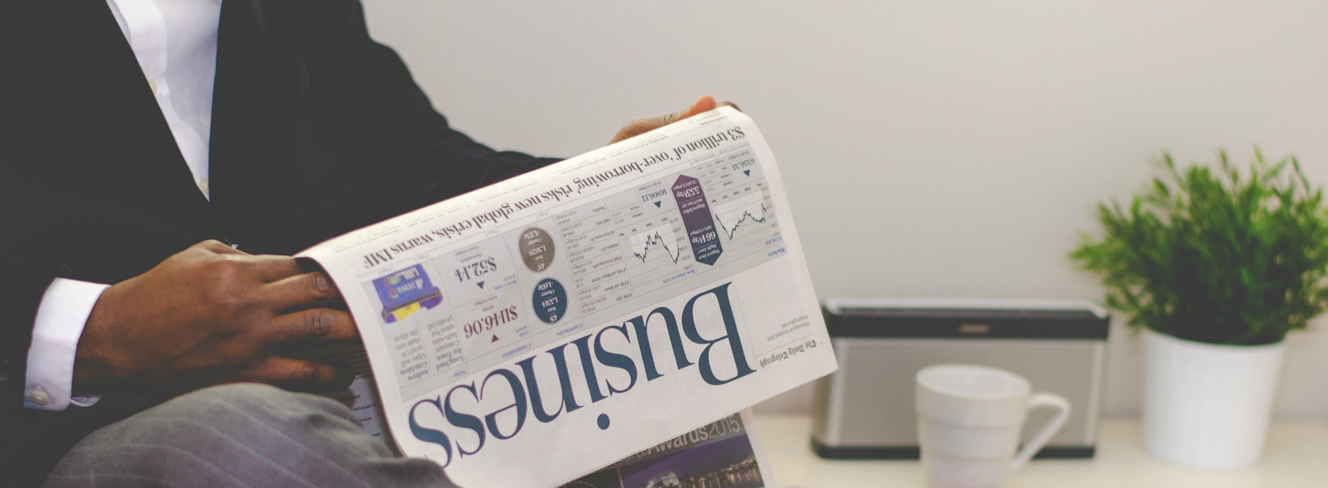 A businessman reading the business section of the newspaper to prepare for his English conversation interview.