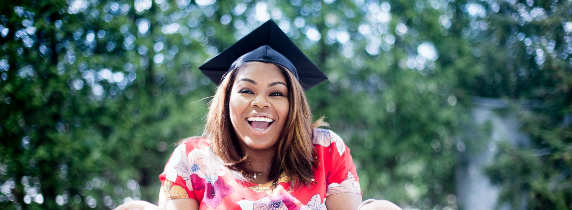A smiling woman wears a graduation cap after writing an effective university motivation letter.