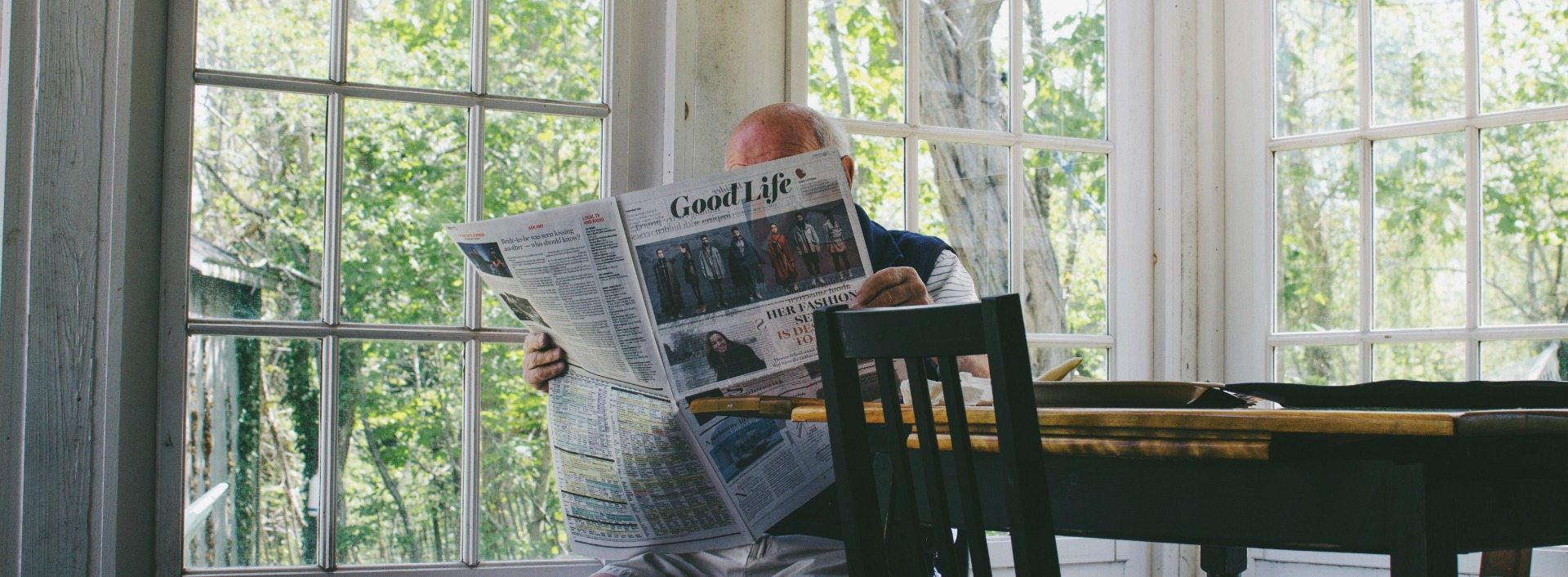 A man is reading the news headlines of the newspaper to learn better English.