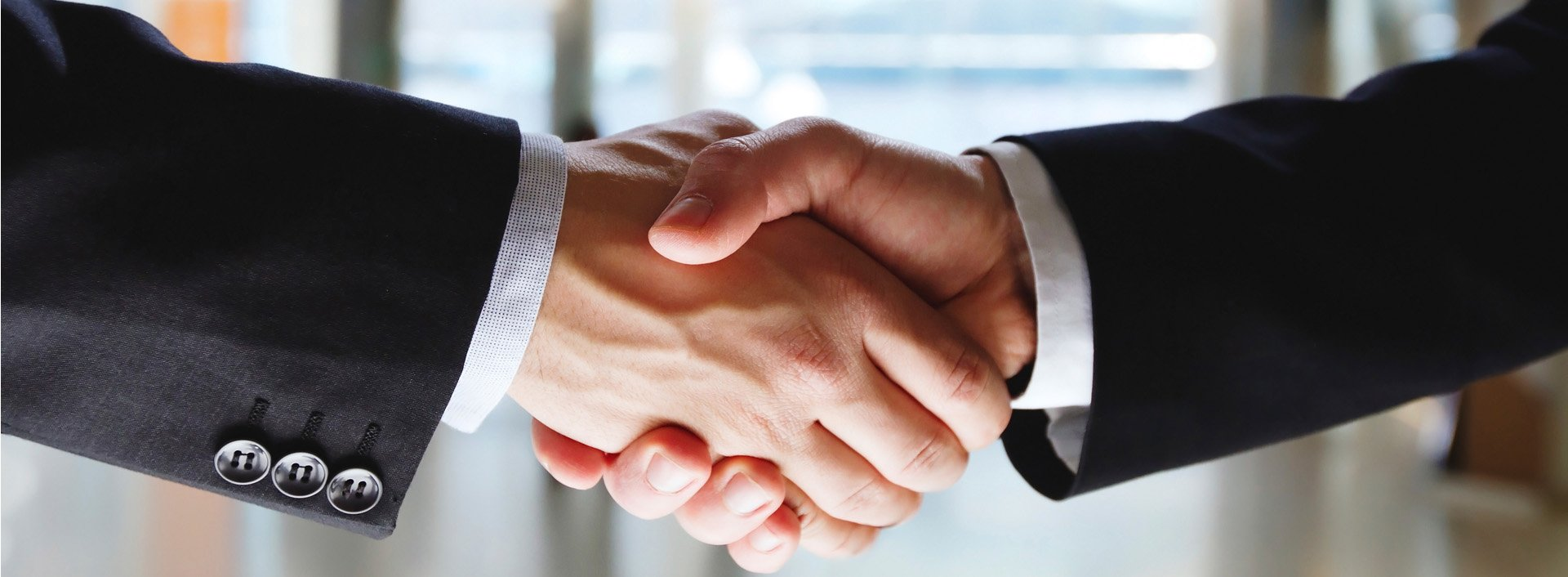 Zwei Geschäftsleute schütteln sich nach einem erfolgreichen englischen Vorstellungsgespräch die Hand.