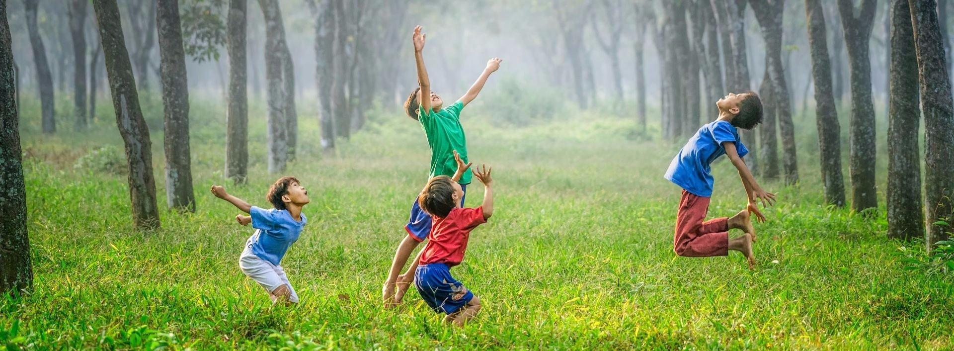 Kinder, die auf einem Feld spielen und einfache englische Sätze verwenden.