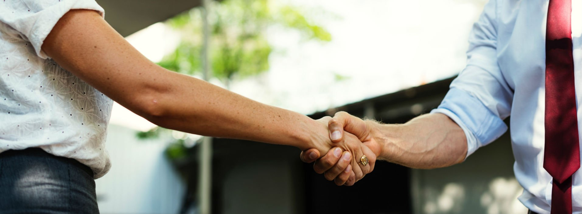 Degrees of Politeness in English- two men shaking hands in formal business attire