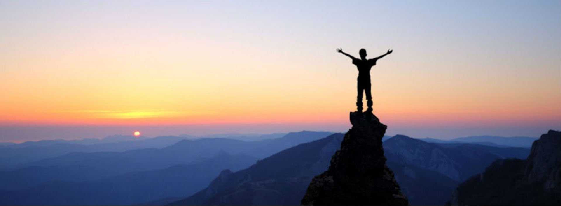 Man standing on mountain top looking over a sunset, words of possibility