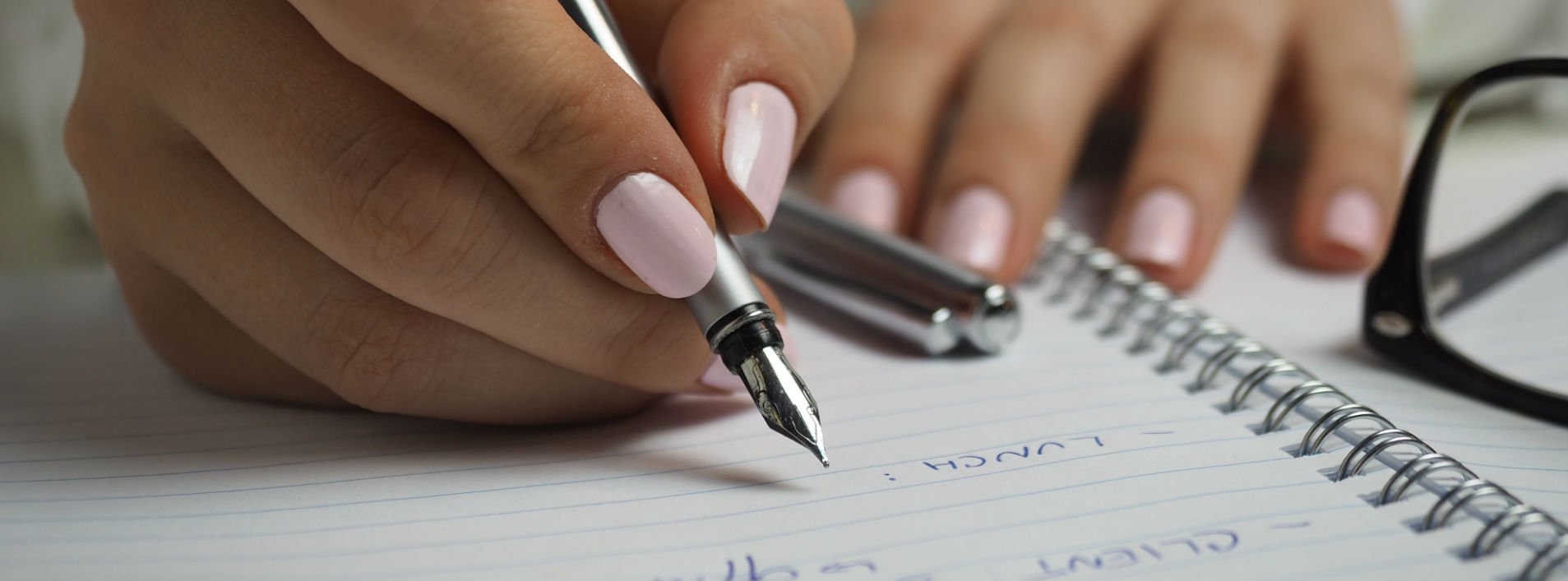 Woman with light pink nails using a fountain pen on a piece of paper and proofreading.