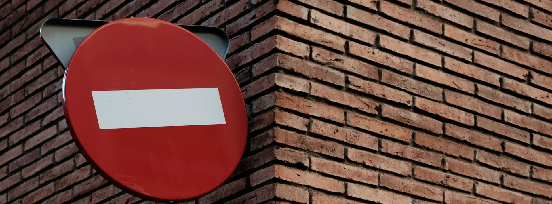 A do not enter sign against the corner of a brick wall- negative prefixes