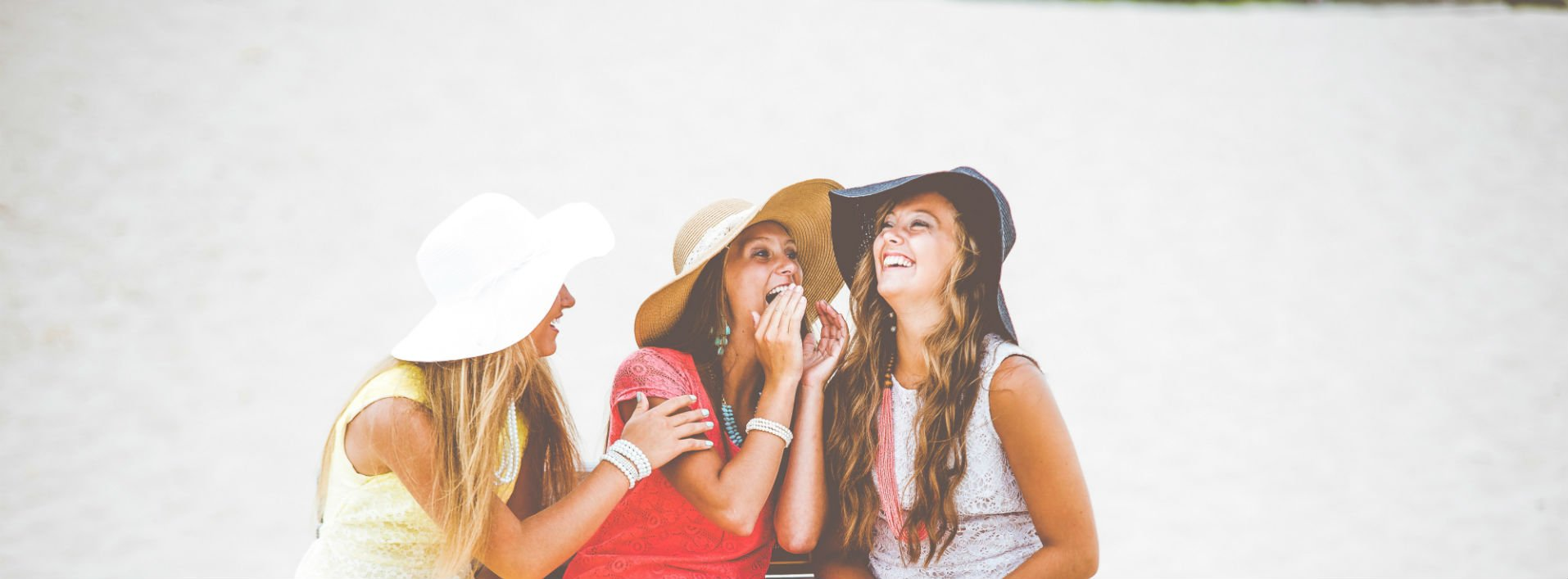 Three girls in white wide-brimmed beach hats laughing at innuendos in English.