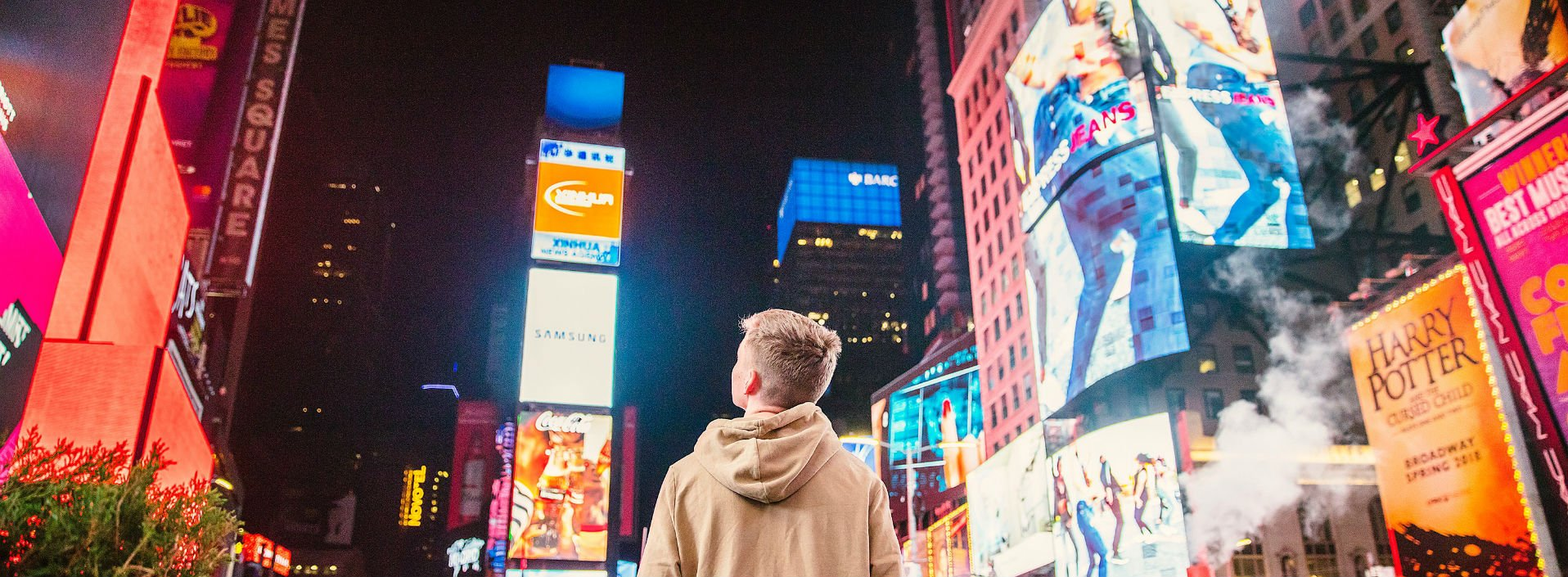 Man standing in Times Square looking at advertisements on the buildings showing marketing terms in English.