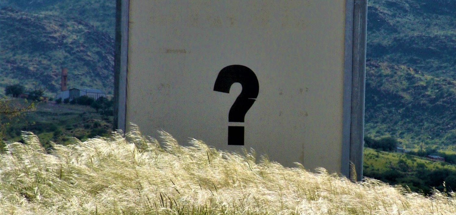 Commonly Confused Words - a wall in a field with a painted question mark on it.