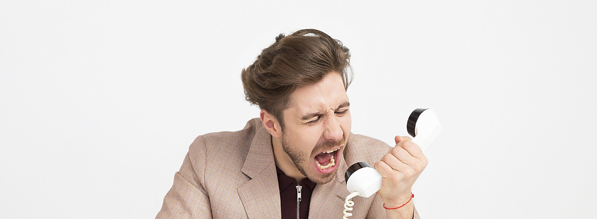 A man sitting at a desk, yelling into a white cord phone screaming in angry English.