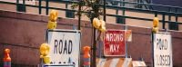 """Signs on the street that say """"Road Words"""" and """"Wrong Way"""" to symbolize popular mistakes in English."""