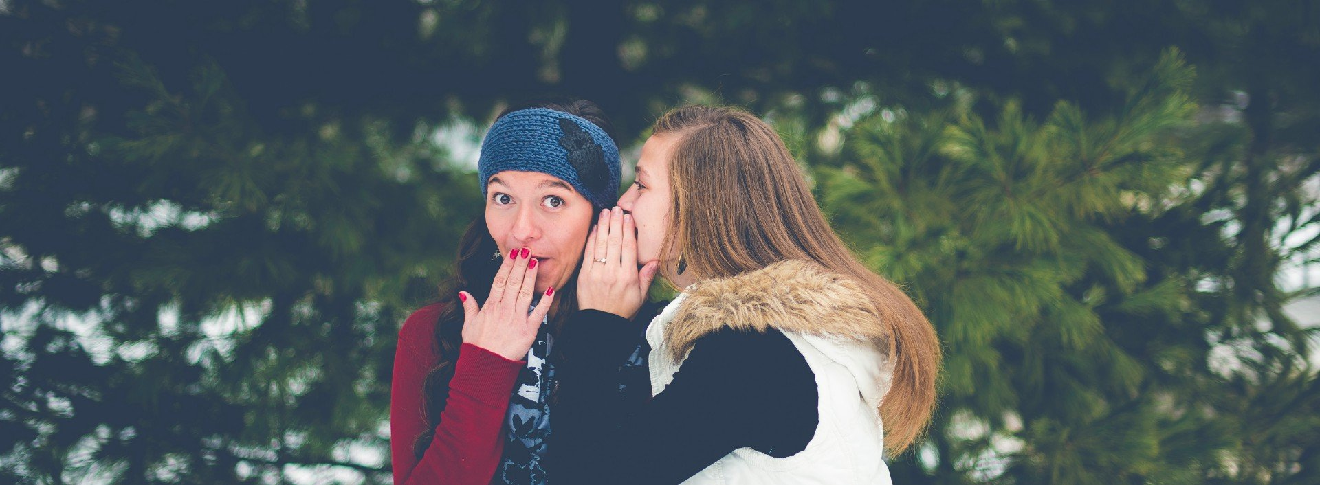 Two girls whispering spoken English to each other.