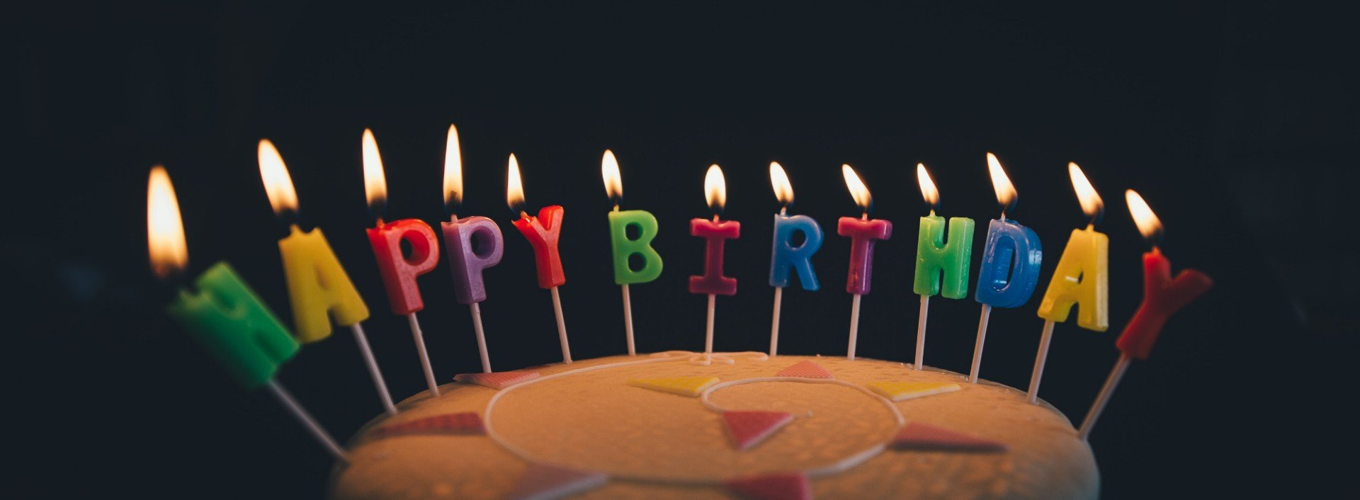 """Birthday cake with a candles that spell the birthday English phrase """"Happy Birthday"""""""