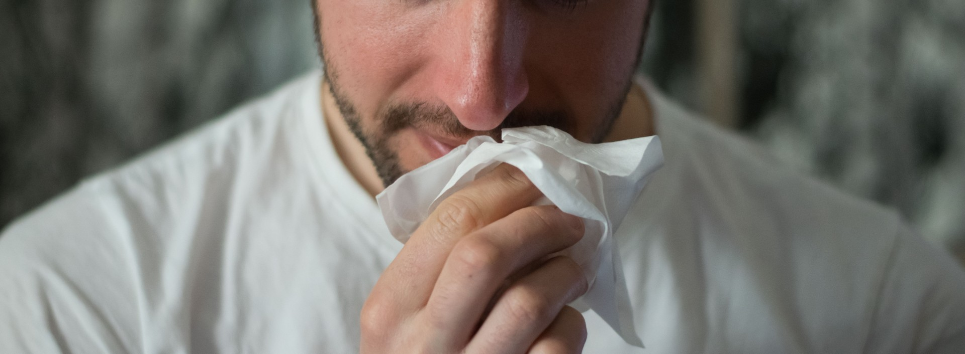A man is rubbing his runny nose with a tissue, health English phrases