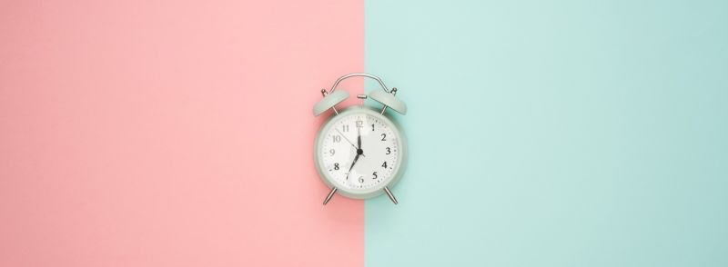 An old alark clock telling time in English: 12:35 on the face, the background is colored pink on the left side and green on the right side.
