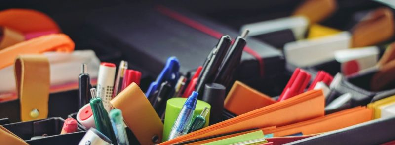 Office supplies in a desk organizer on a desk.
