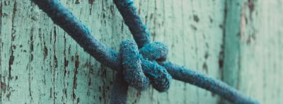 A close up picture of a rope tied in a knot on a wall to show root word LIG means to tie