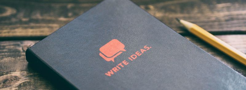 """A cover of a black book with the words """"write ideas"""" underneath two speech bubbles to exchange ideas in English."""