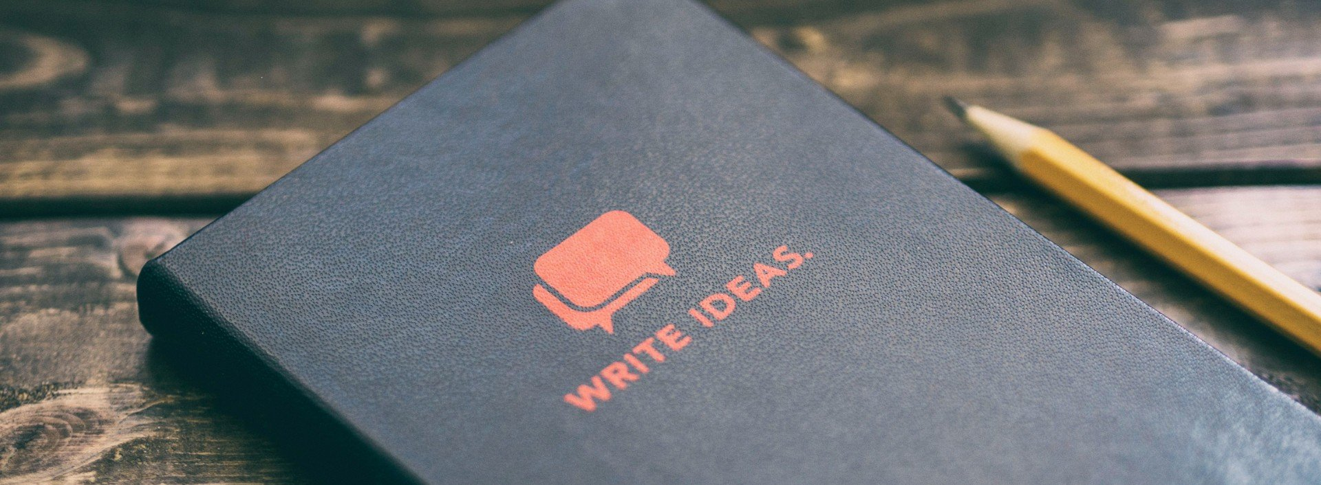 "A cover of a black book with the words ""write ideas"" underneath two speech bubbles to exchange ideas in English."
