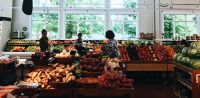 Going grocery shopping in English in the produce section, shoppers in the produce section looking at different produce on the shelves.