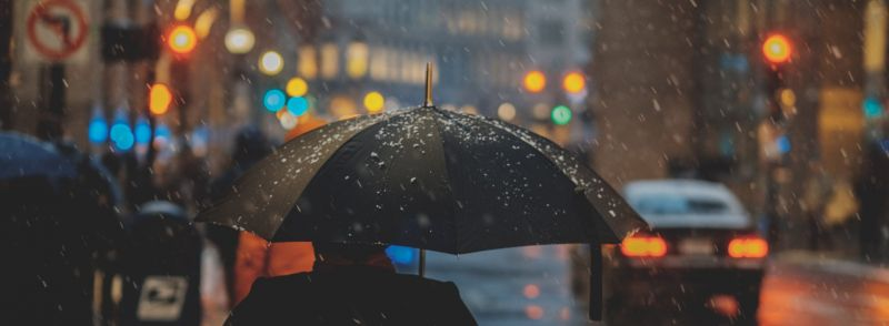 Man walking in light snow holding a black umbrella on a busy city street: easy weather words