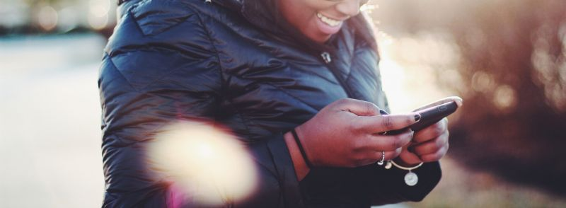 A close up of a woman in a big black jacket texting acronyms on her smartphone while smiling.