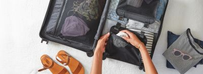 A woman packing clothes into a suitcase while using travel phrases for beginners.