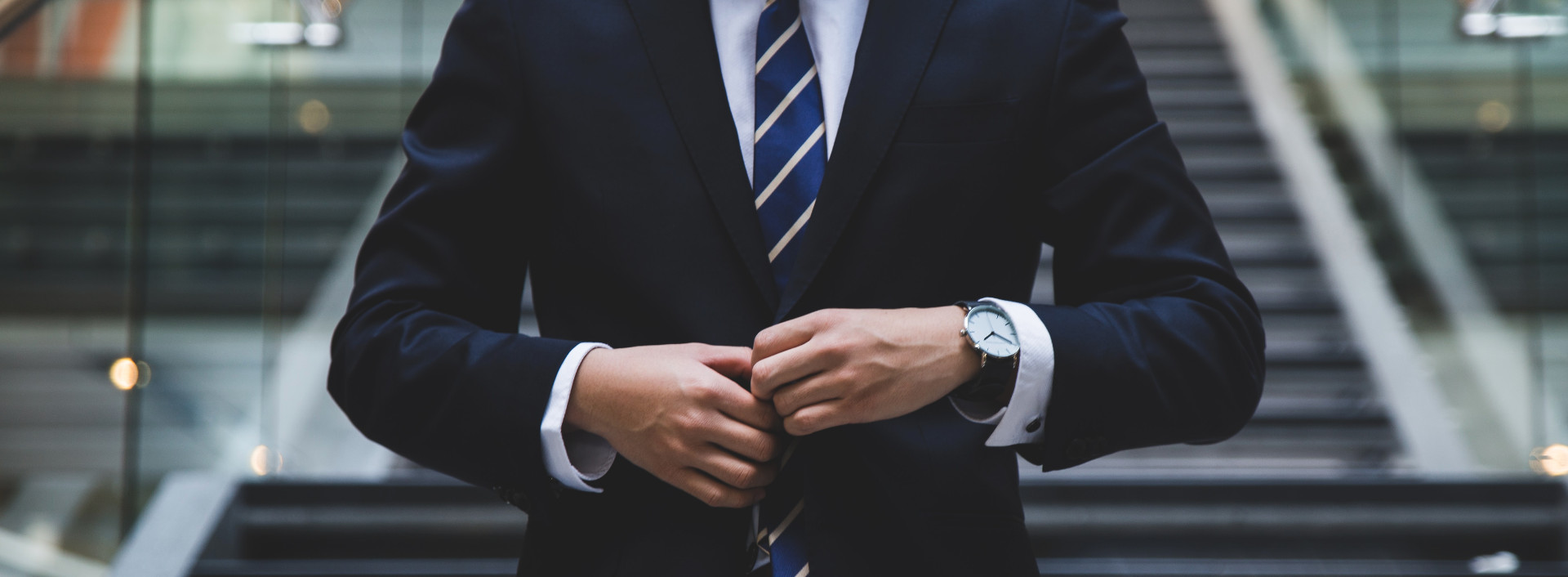 Job Titles in English: Close up image of a man buttoning a suit jacket.