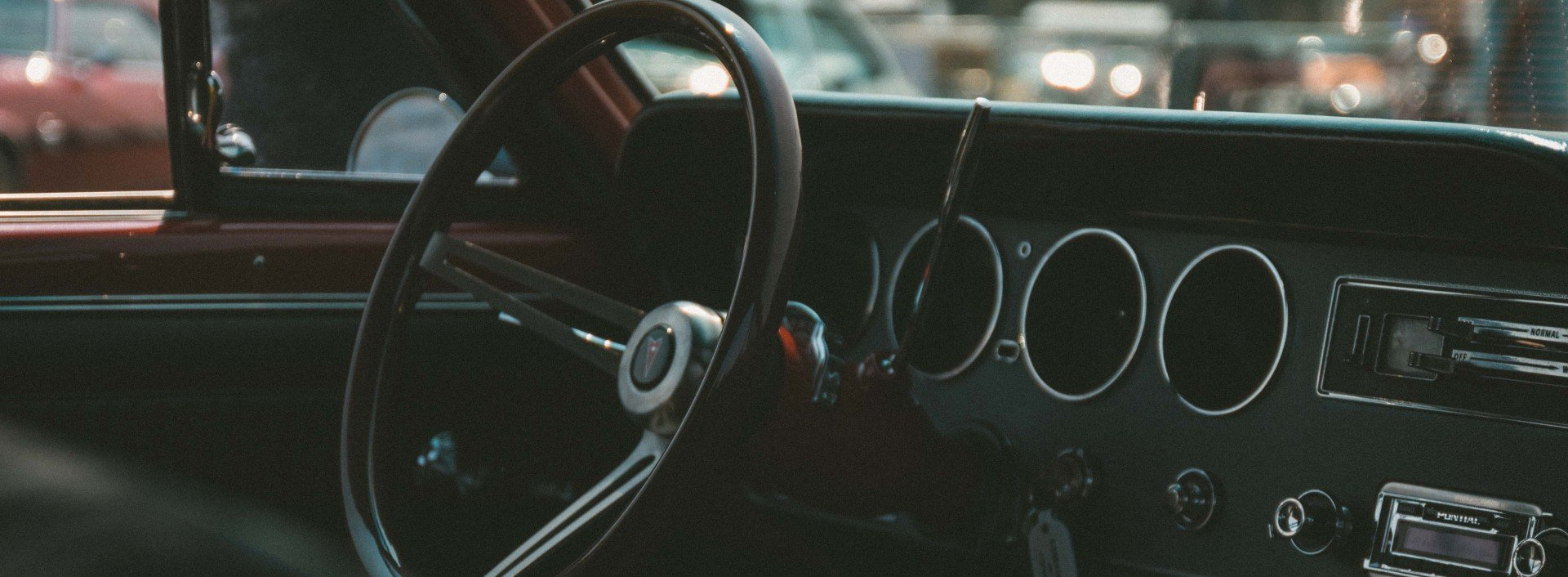 A steering wheel and the dashboard, two important car parts in English, are shown in an old style car.