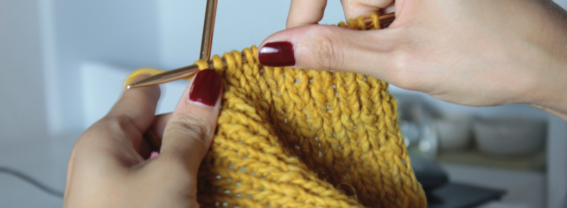Two hands with red fingernails knit with yellow yarn while learning knitting vocabulary.