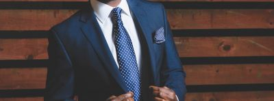 A man wears a dark blue suit with a white shirt and a blue tie with white polka dots. Suits and ties are essential parts of men's formal wear in English.