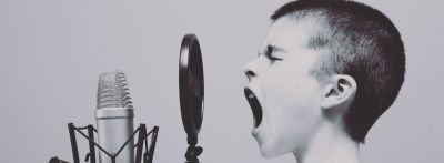 Sounds things make in English: A boy with a shaved head yells into a a recording microphone.
