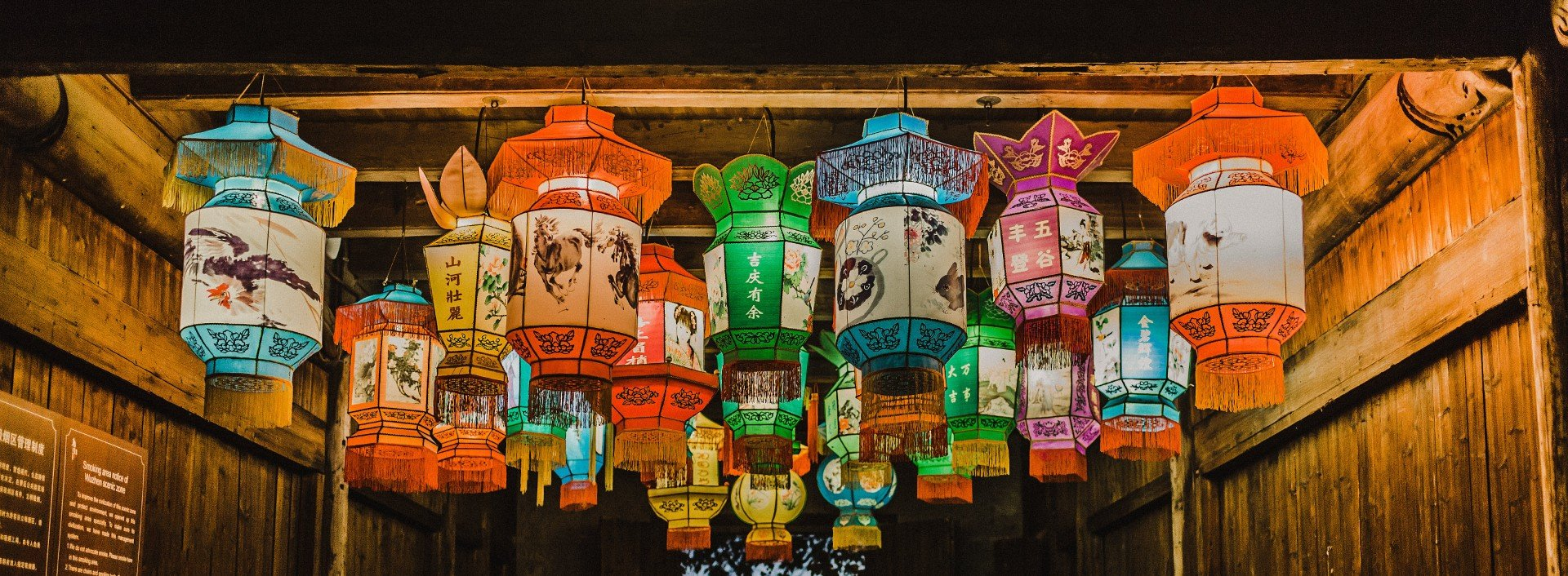 Chinese Loan Words: Many different colored lanterns with Chinese writing and paintings on them hang from a ceiling.