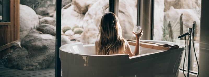 A woman sits in a bathtub in front of a window with a drink after studying some vocabulary for being at home.