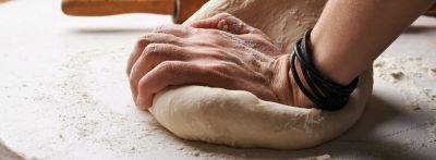 A person kneads bread dough next to a rolling pin while using baking vocabulary in English.