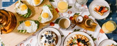 Breakfast vocabulary: a breakfast table is completely laid out, with eggs, coffee, waffles, and fruit.
