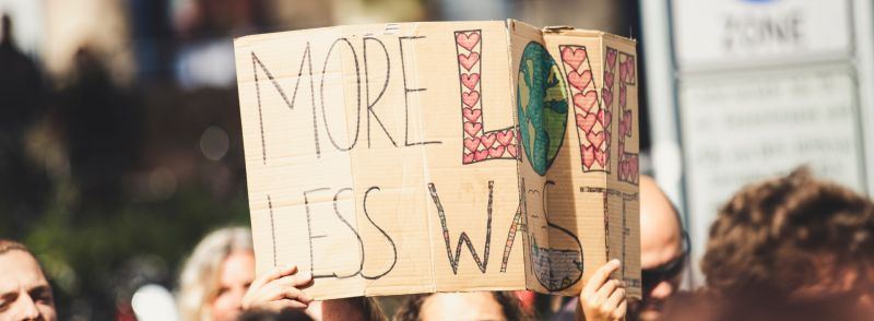 """A sign reads """"more love, less waste,"""" a good example of the difference between fewer vs. less."""