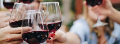 Three friends toast each other with wine glasses. To toast is an important wine vocabulary in English.