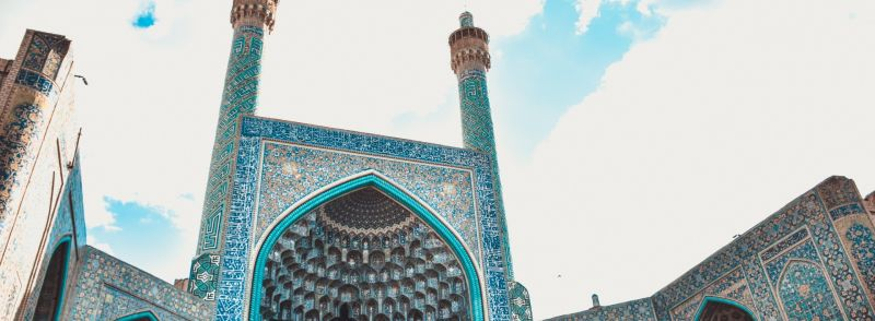 Persian loan words: A mosque with a blue mosaic in front of a blue sky in Iran.