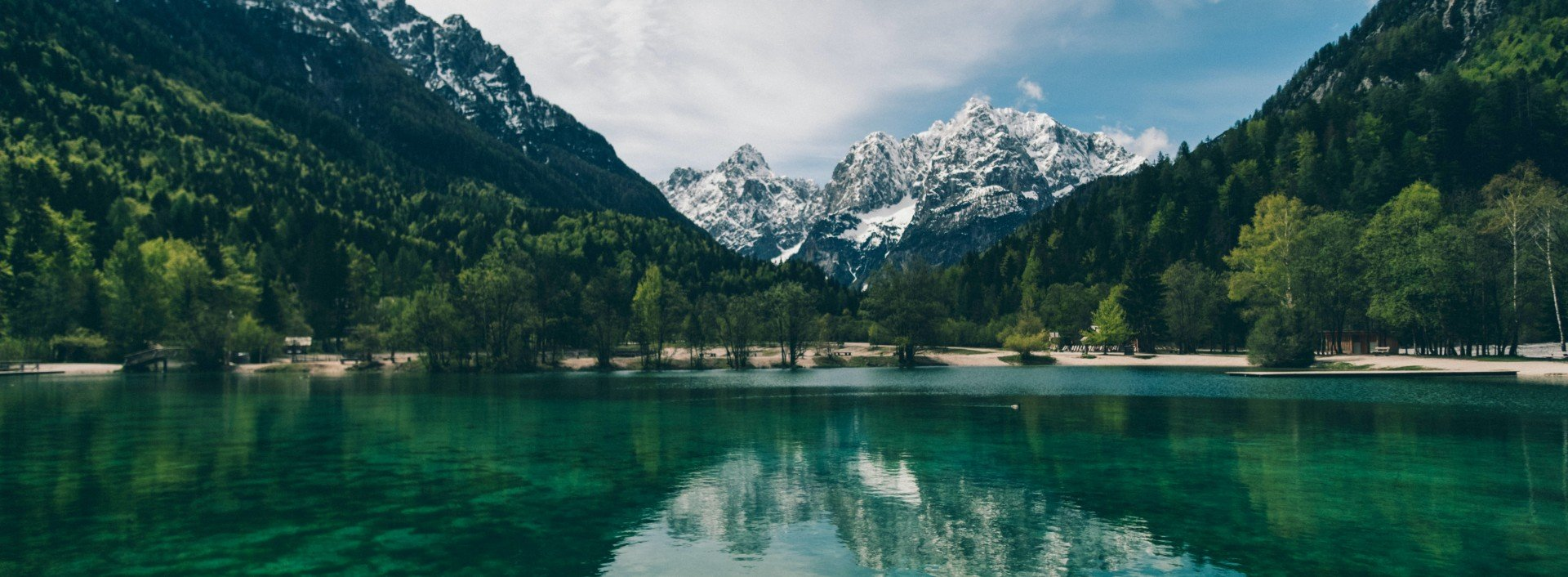 Water Vocabulary in English: A crystal clear lake sits in front of a mountain covered in snow.