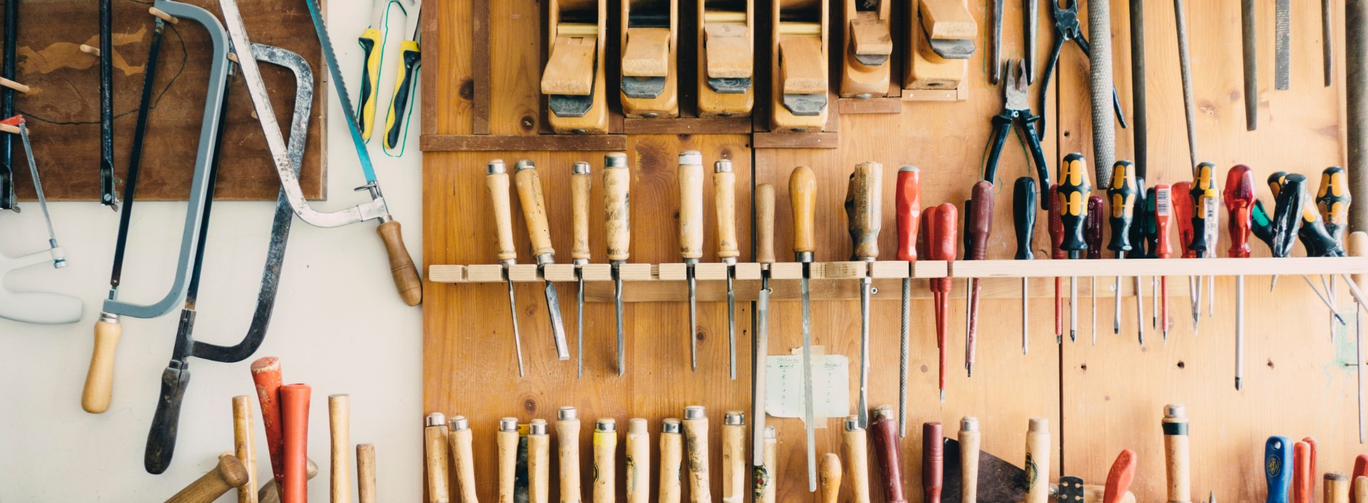 An assortment of tools, such as screwdrivers, hammers, and saws hang on a wall. These are all useful tools vocabulary in English.