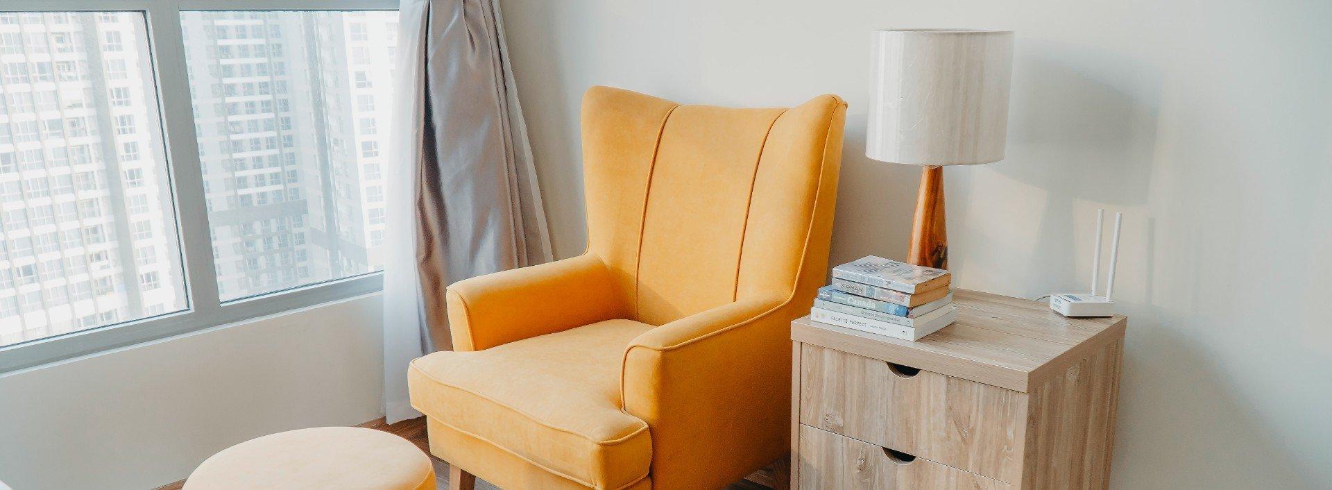 Ein gelber Sessel und ein Nachttisch stehen in einem weißen Zimmer. Sessel und Nachttisch als englische Wörter für Möbel sind praktisch zu kennen
