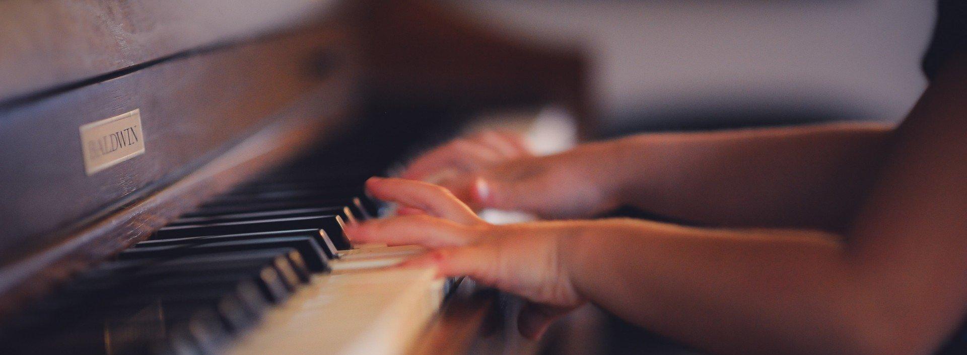 Redewendungen mit get: Ein Kind lernt Klavier zu spielen und bekommt den Dreh raus