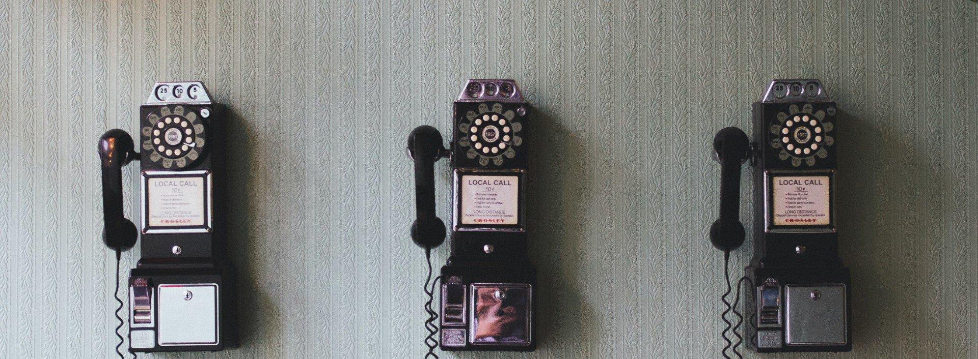 Root word loqu: three vintage telephones are lined up on a wall.