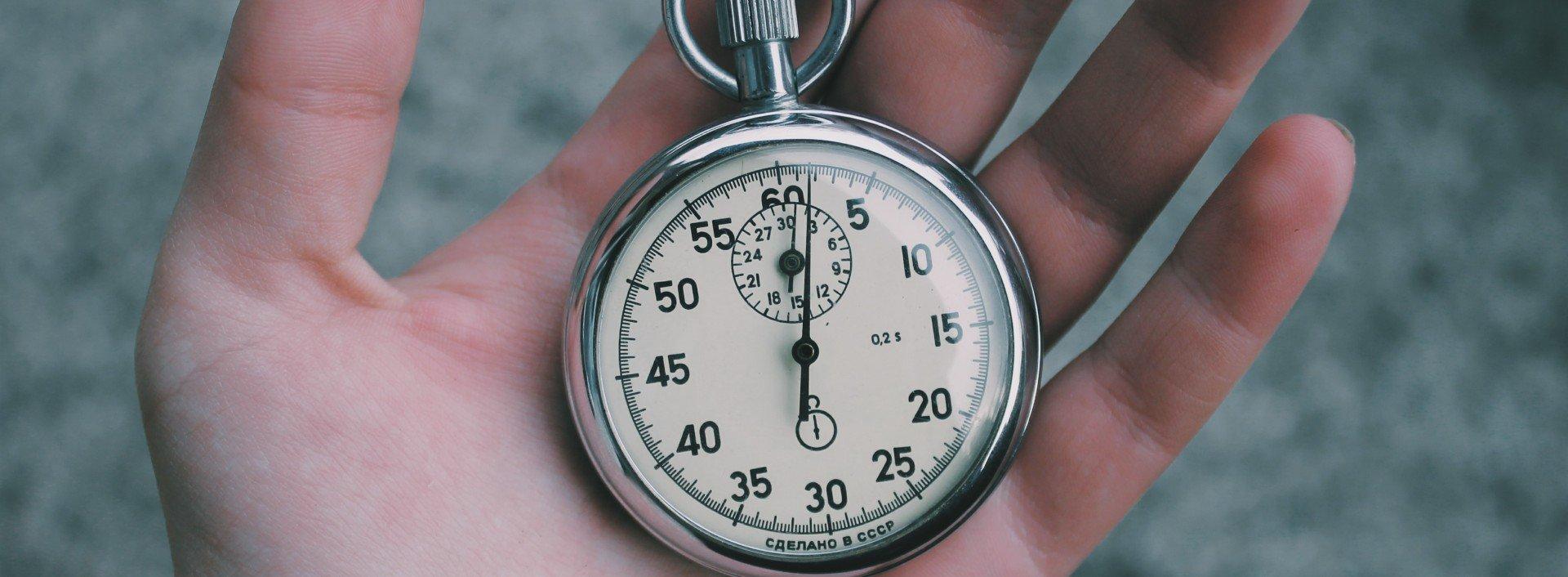 Eine Person hält eine Stoppuhr. Minute ist eines der vielen Heteronyme im Englischen.