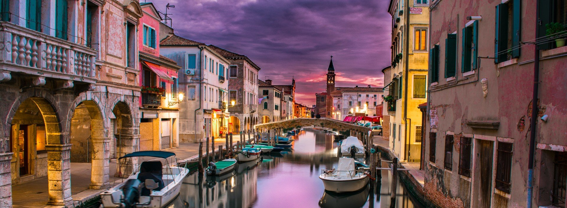 Italian Loan Words in English: A canal in Venice at sunset with the sunset reflecting off the water.