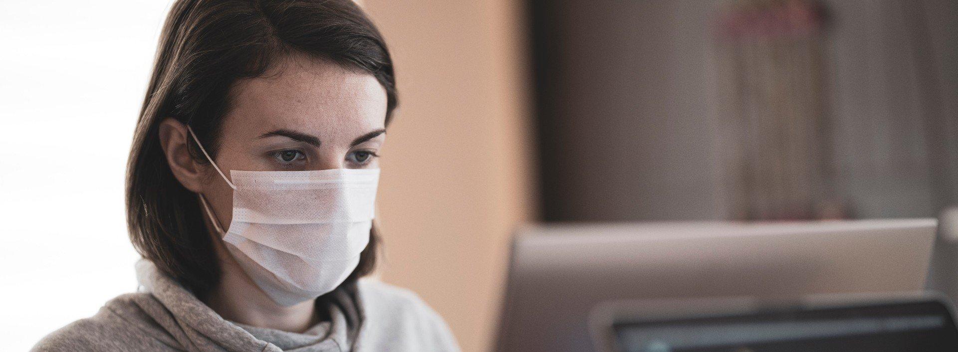 Coronavirus-Pandemie-Vokabeln: Eine Frau trägt an ihrem Schreibtisch eine Maske, um die Verbreitung von COVID-19 zu verhindern.