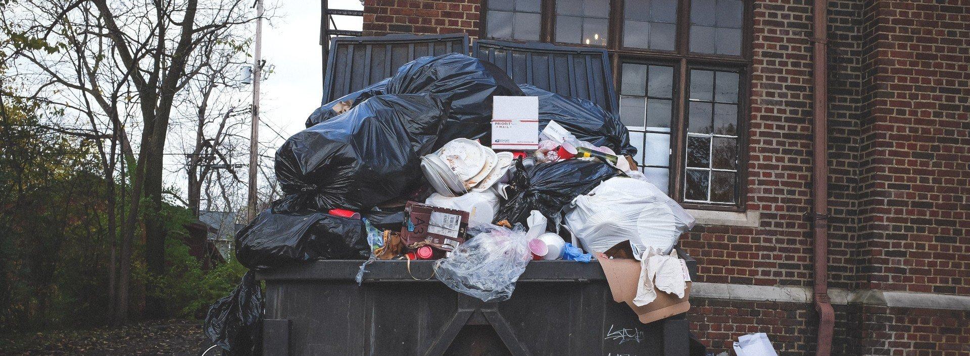 Englische Vokabeln für verdorbenes Essen: Ein Müllcontainer quillt über vor Müll und verdorbenen Lebensmitteln.