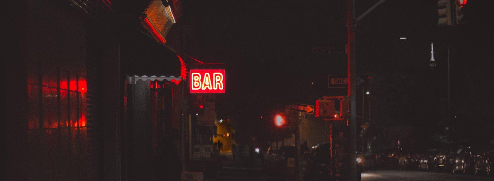 """Barvokabeln auf Englisch: Eine Leuchtreklame mit der Aufschrift """"Bar"""" leuchtet nachts an einer Straße."""