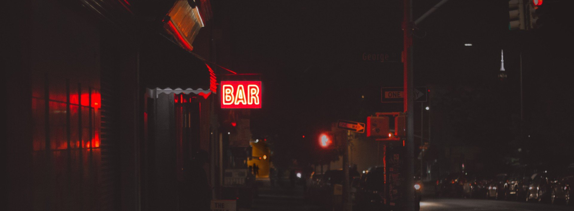 """Bar vocabulary in English: a neon sign reading """"bar"""" is lit up on a street at night."""